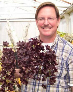 photo of Fred Clarke with Fredclarkeara orchid